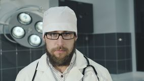 Retrato del doctor serio hermoso que mira la cámara 4K almacen de video