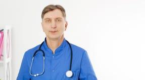 Retrato del doctor sonriente que presenta con la oficina, él está llevando un estetoscopio, el espacio de la copia para el logoti fotografía de archivo libre de regalías