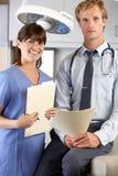 Retrato del doctor y de la enfermera en Office del doctor Imagen de archivo libre de regalías