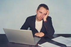 Retrato del dolor de cabeza masculino cansado de la sensación mientras que trabaja con el ordenador portátil en la tabla Cansanci Imágenes de archivo libres de regalías
