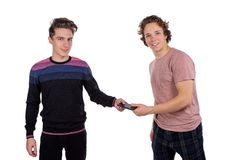 Retrato del dos hombres jovenes felices usando los teléfonos móviles aislados sobre el fondo blanco imagen de archivo libre de regalías