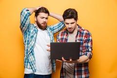 Retrato del dos hombres jovenes trastornados que usan el ordenador portátil imagen de archivo libre de regalías