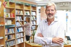 Retrato del dueño masculino de la librería con el cliente en fondo foto de archivo