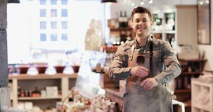 Retrato del dueño masculino sonriente de la tienda de la charcutería almacen de video