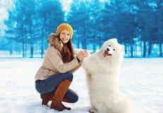 Retrato del dueño feliz de la mujer que se divierte con el perro blanco del samoyedo Foto de archivo