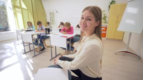 Retrato del educador joven femenino durante la lección de enseñanza con los principiantes en sala de clase en la escuela primaria almacen de metraje de vídeo