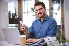 Retrato del ejecutivo confiado que usa el teléfono móvil en la oficina creativa foto de archivo libre de regalías