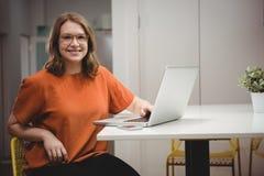 Retrato del ejecutivo de sexo femenino sonriente que usa el ordenador portátil imágenes de archivo libres de regalías