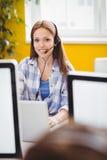 Retrato del ejecutivo hermoso con los auriculares usando el ordenador portátil en la oficina creativa Fotografía de archivo libre de regalías