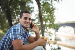 Retrato del ejecutivo que habla en el teléfono móvil mientras que comiendo el plátano imagen de archivo