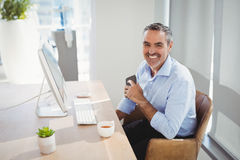 Retrato del ejecutivo sonriente que se sienta en el escritorio fotos de archivo