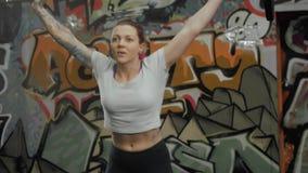 Retrato del ejercicio de ejecución femenino del deadlift con la barra del peso Mujer joven confiada que hace entrenamiento del le almacen de metraje de vídeo