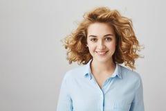 Retrato del empleado atractivo confiado con el pelo rizado corto, blusa de la oficina que lleva mientras que sonríe ampliamente y Fotos de archivo