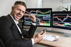 Retrato del empleado de sexo masculino que usa el teléfono móvil mientras que trabaja con los gráficos digitales en el ordenador  fotografía de archivo