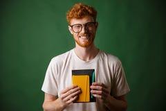 Retrato del empollón barbudo sonriente del readhead, sosteniendo el cuaderno y Imágenes de archivo libres de regalías