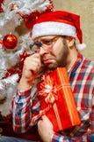 Retrato del empollón triste con el regalo de la Navidad en el sombrero de santa Imágenes de archivo libres de regalías