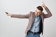 Retrato del empresario de sexo masculino joven apuesto feliz divertido en la chaqueta y los vidrios que bailan sacudiendo sostene fotografía de archivo libre de regalías