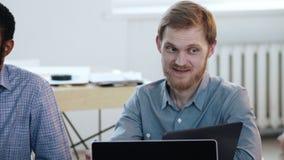 Retrato del encargado corporativo de sexo masculino sonriente joven feliz que se sienta en la mesa de reuniones del equipo en ofi metrajes