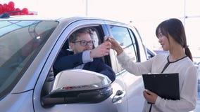 Retrato del encargado de ventas del coche con el par joven del comprador que muestra llaves dentro de la máquina mientras que com metrajes