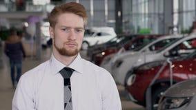 Retrato del encargado joven que se coloca en el autocentro, cámara lenta metrajes