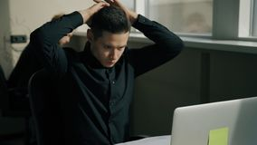 Retrato del encargado joven que trabaja en el ordenador portátil en la oficina con el colega masculino en el fondo almacen de metraje de vídeo