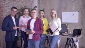 Retrato del equipo de trabajo acertado, del varón sonriente del negocio y de mujeres durante horas de trabajo en oficina almacen de video