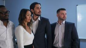 Retrato del equipo del negocio que se coloca en oficina almacen de metraje de vídeo