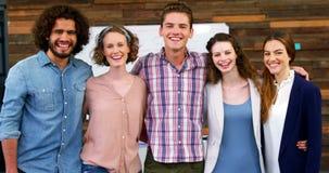 Retrato del equipo feliz del negocio que se coloca con los brazos alrededor metrajes
