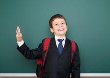 Retrato del escolar en traje negro en el fondo verde con la mochila roja, concepto de la pizarra de la educación Fotos de archivo