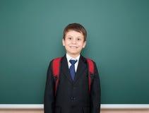Retrato del escolar en traje negro en el fondo verde con la mochila roja, concepto de la pizarra de la educación Imagenes de archivo
