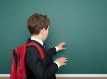 Retrato del escolar en traje negro en el fondo verde con la mochila roja, concepto de la pizarra de la educación Fotografía de archivo