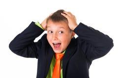 Retrato del escolar inteligente desconcertante con las manos en la cabeza, fondo blanco Imagen de archivo