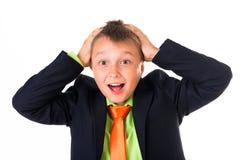 Retrato del escolar inteligente desconcertante con las manos en la cabeza, fondo blanco Imágenes de archivo libres de regalías