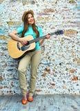 Retrato del estilo del adolescente de la mujer joven que toca la guitarra acústica Foto de archivo libre de regalías