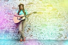 Retrato del estilo del adolescente de la mujer joven que toca la guitarra acústica Fotos de archivo