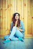 Retrato del estilo de la juventud de la mujer joven que se sienta en un piso Fotografía de archivo libre de regalías