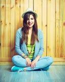Retrato del estilo de la juventud de la mujer joven que se sienta en un piso Foto de archivo