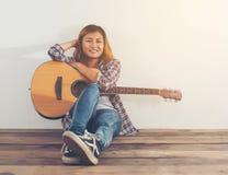 Retrato del estilo de la mujer del inconformista que se enfría con la mirada de la guitarra tan feliz Fotos de archivo