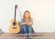 Retrato del estilo de la mujer del inconformista que se enfría con la mirada de la guitarra tan feliz Imagen de archivo libre de regalías