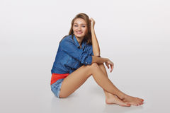 Retrato del estilo del dril de algodón de la muchacha adolescente en el piso, sobre backgr gris Imagen de archivo libre de regalías