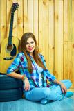 Retrato del estilo del inconformista de la muchacha sonriente que se sienta en un piso Imagen de archivo