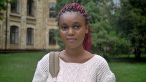 Retrato del estudiante africano hermoso joven que mira la cámara y la situación en parque cerca de la universidad, mujer encantad metrajes