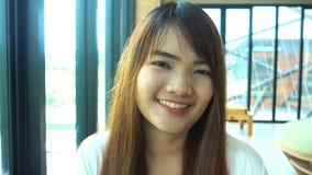 Retrato del estudiante asiático hermoso sonriente que se coloca en biblioteca almacen de metraje de vídeo