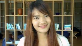 Retrato del estudiante asiático hermoso sonriente que se coloca en biblioteca Estantes del estante para libros en fondo metrajes