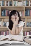 Retrato del estudiante asustado en biblioteca Foto de archivo libre de regalías
