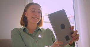 Retrato del estudiante atractivo joven que habla en videochat en la tableta que se sienta en el sofá en sala de estar metrajes