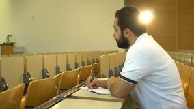 Retrato del estudiante atractivo joven que se sienta en la sala de conferencias, Magdeburgo, Alemania 01 09 2018 almacen de video