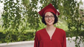 Retrato del estudiante de graduación alegre de la mujer joven en vestido y del mortero-tablero que sonríe y que mira la cámara qu metrajes