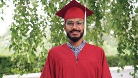 Retrato del estudiante de graduación barbudo del hombre de la raza mixta en vestido y del mortero-tablero que sonríe y que mira l almacen de video