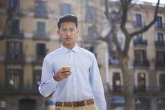 Retrato del estudiante elegante en las lentes que sostienen el teléfono móvil disponible Imagen de archivo